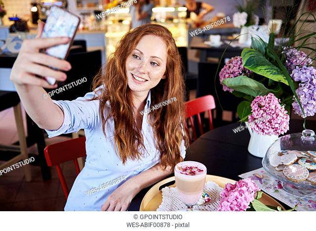 Smiling young woman taking a selfie in a cafe