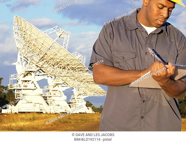 African man writing on clipboard with radio telescopes in background