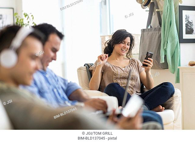 Hispanic friends using technology in living room