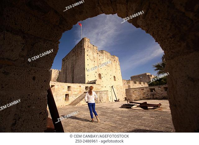 Framed view to the Cesme castle with a tourist in the foreground, Izmir, Turkey, Europe