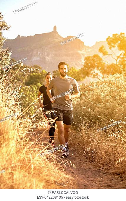Young couple jogging on a gravel path in the late afternoon sunshine with trees behind, while wearing casual clothing