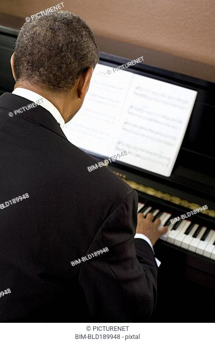 Rear view of African man playing piano