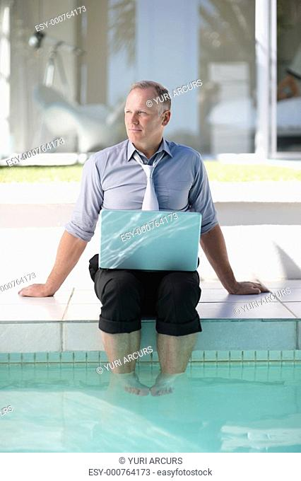 Business man on vacation using a laptop by the swimming pool