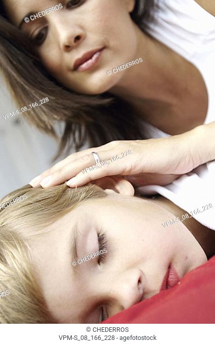 Close-up of a boy sleeping with his mother looking at him
