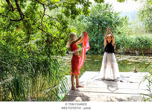 Two girls standing on jetty at a pond in fancy dresses