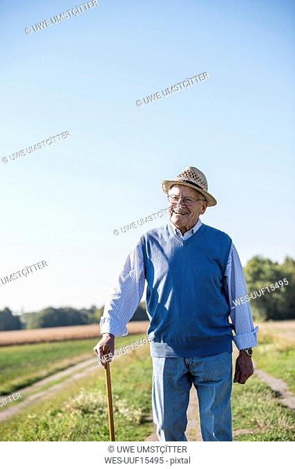 Senior man with a walking stick, walking in the fields