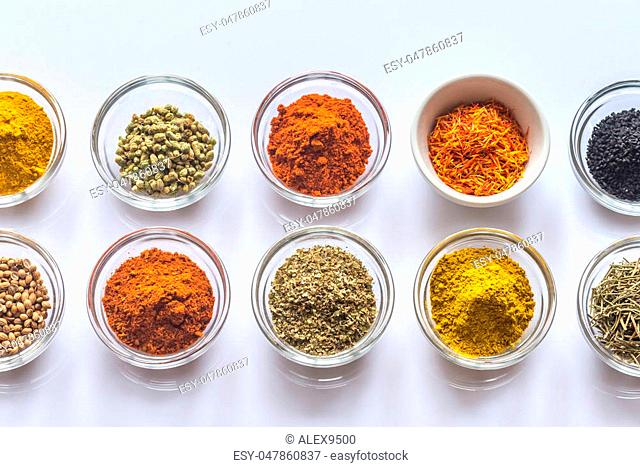 Different kinds of spices and herbs on the white background