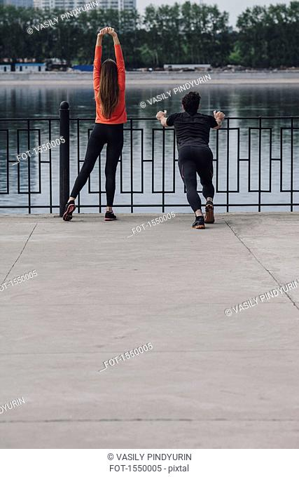 Rear view of people stretching on promenade next to lake