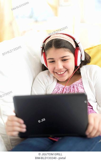 Hispanic girl using digital tablet on sofa