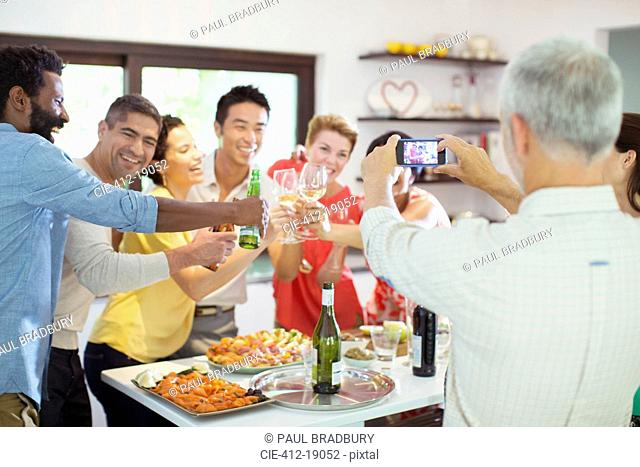 Man taking picture of friends at party