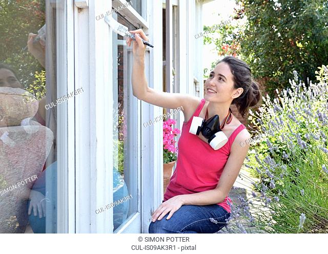 Young woman sitting painting house window