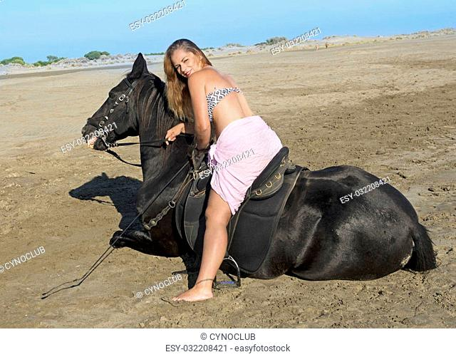 horse woman and her stallion lying down on the beach
