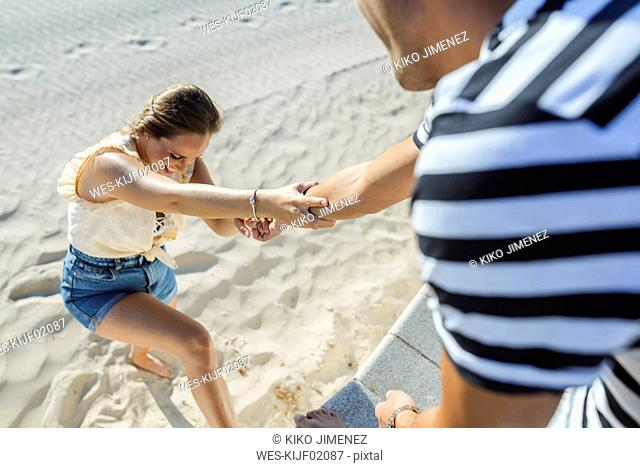 Man helping woman to climb up from the beach