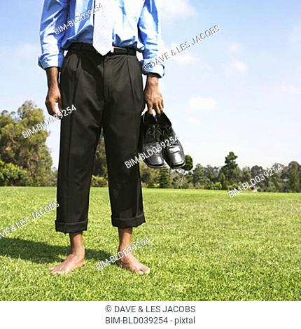 African businessman with bare feet in field