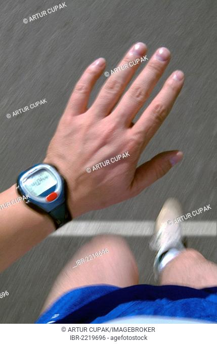 Runner looking at a heart rate monitor