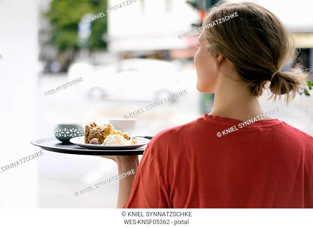 Rear viewof young woman serving coffee and cake in a cafe
