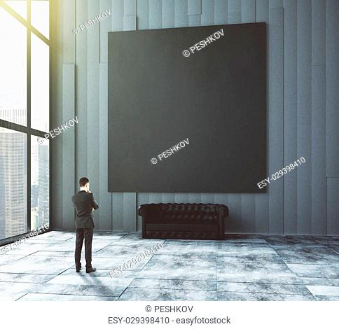 Businessman looks at big blank picture above leather sofa in empty loft room with big windows and concrete floor