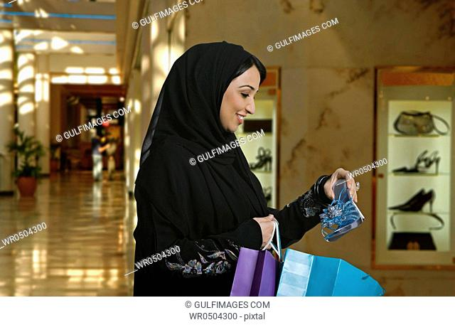 Young woman holding shopping bag and sandal