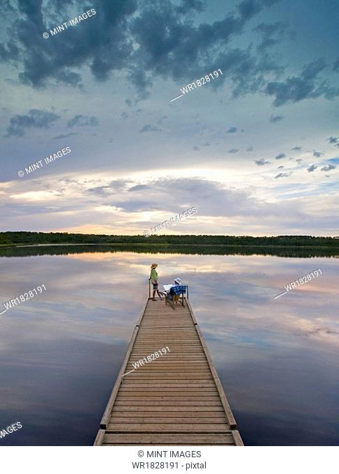 A couple, man and woman sitting at the end of a long wooden dock reaching out into a calm lake, at sunset