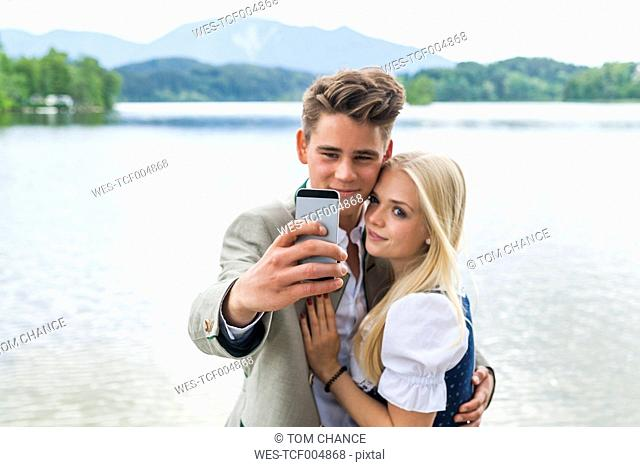 Germany, Bavaria, young couple taking a selfie in front of Staffelsee