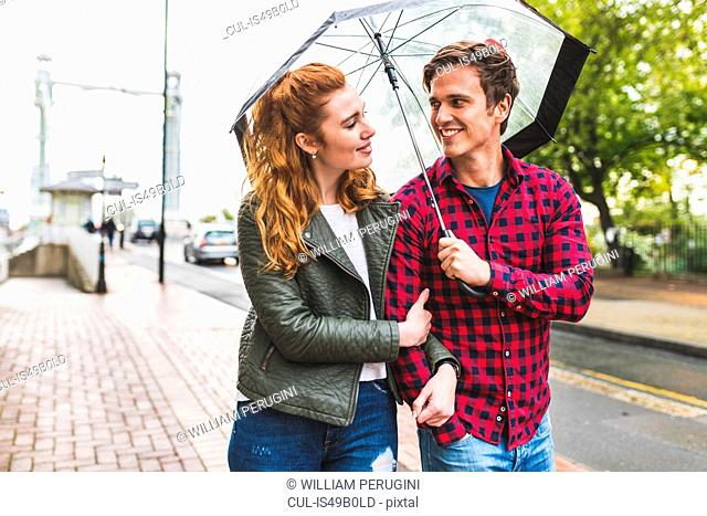 Couple walking together, outdoors in rain, holding umbrella, smiling