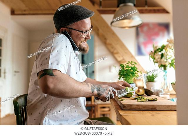 Smiling man on the phone chopping avocado