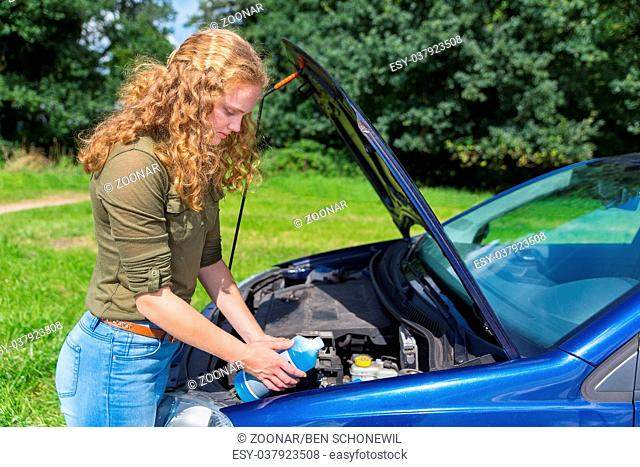 Dutch girl filling car reservoir with fluid in bottle
