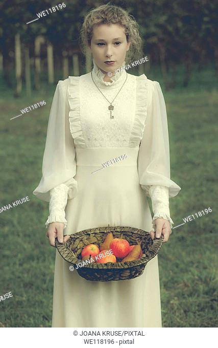 a woman in a white edwardian dress is holding a basket with fruits