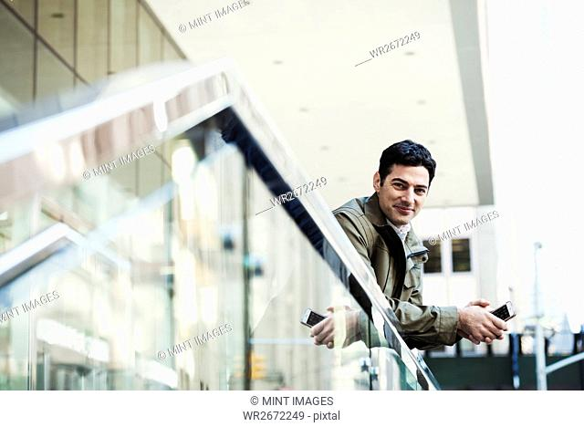 A young man leaning over a balcony rail holding a cellphone and smiling