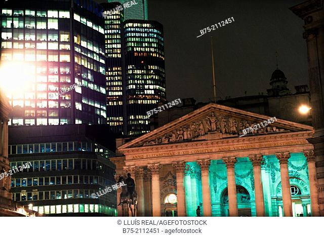 Contrast of modern and ancient buildings. The old Stock Exchange building iluminated at night. City of London, England, UK, Europe