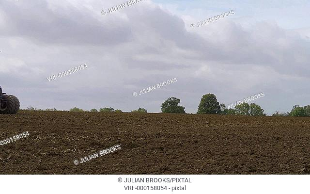 Blue tractor harrowing a field in autumn, across frame
