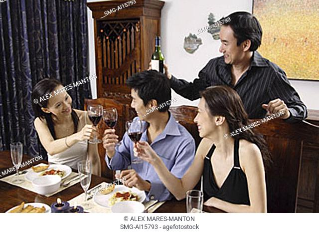 Adults at dining table toasting with wine glasses