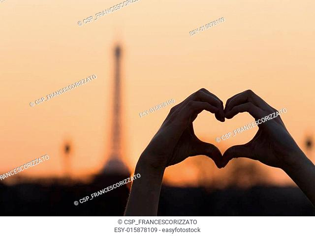 Female Hands Forming a Heart Shape at Sunset in front of the Eif