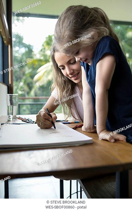 Mother and daughter drawing with crayons