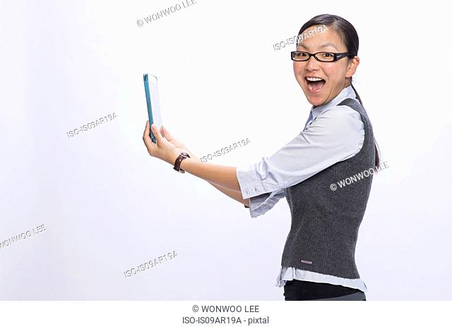 Businesswoman holding digital tablet at arms length