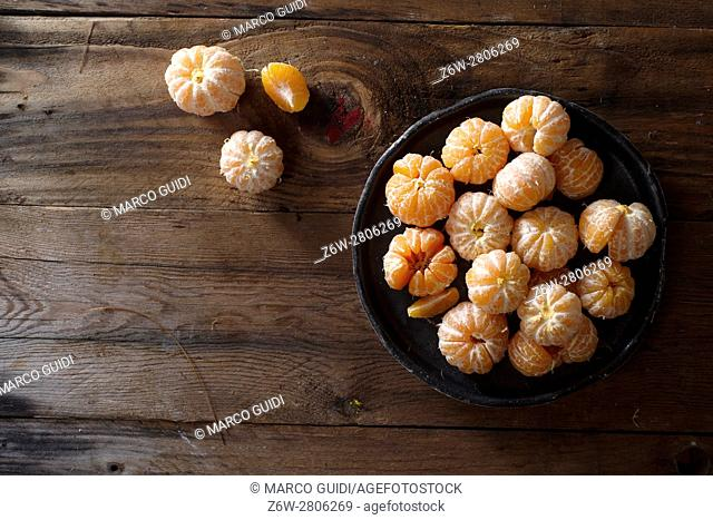 Presentation of a group of peeled mandarins on wooden table