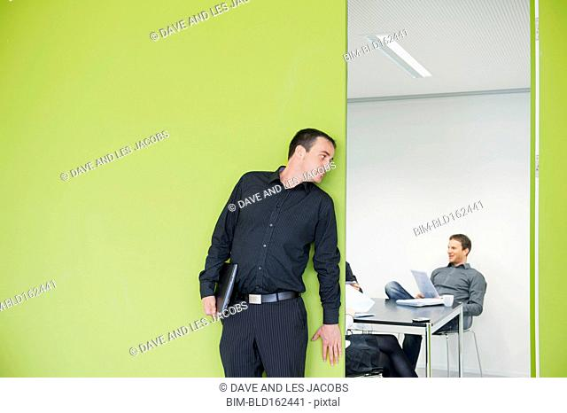 Caucasian businessman eavesdropping on office meeting