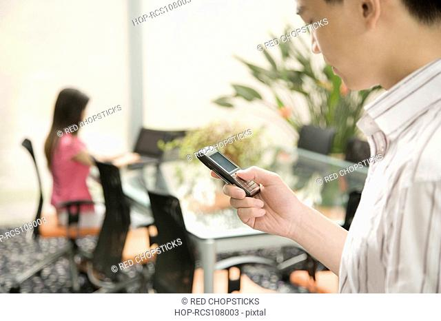 Side profile of a male office worker operating a mobile phone in an office