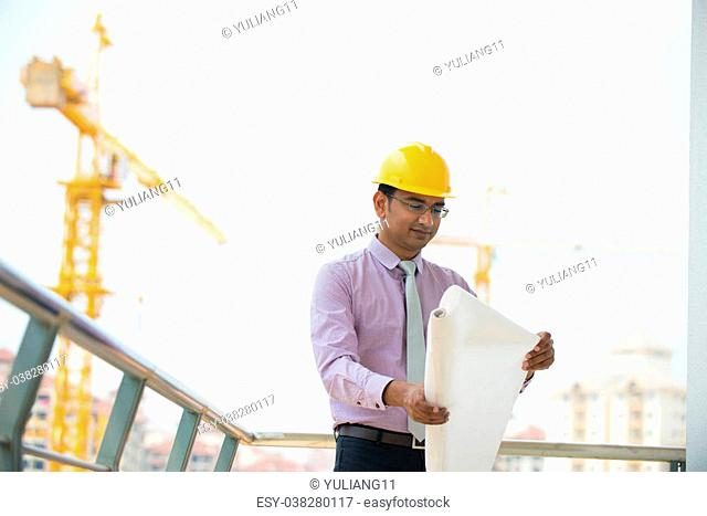 064143ccb06 indian male architect reading plans with construction background
