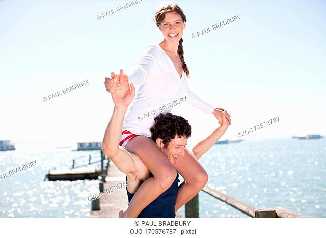 Man carrying wife on shoulders on pier at ocean