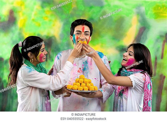 Women feeding a man laddoos
