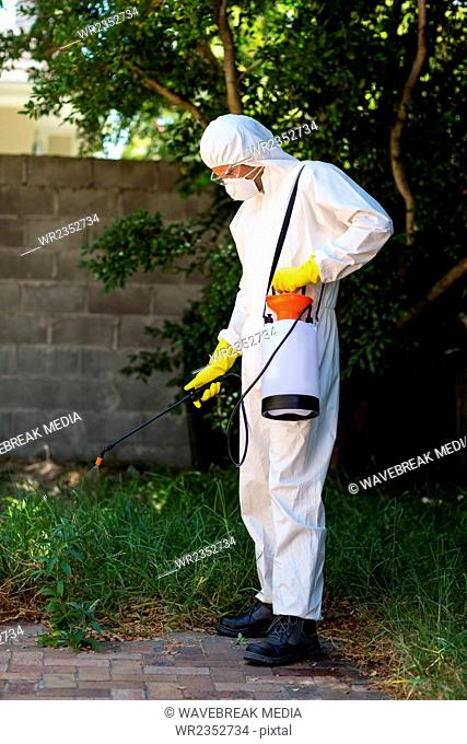 Man in protective workwear while spraying pesticide on grass