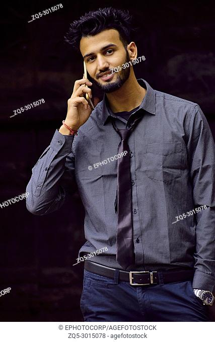 Young man dressed in formal shirt and black tie with cell phone, Pune, Maharashtra