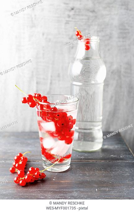 Water with ice cubes, red currants, flavoured