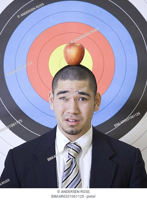 Businessman with apple on head in front of bulls eye
