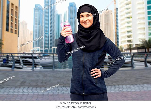 sport, fitness and people concept - happy smiling muslim woman in hijab with water bottle over dubai city street background