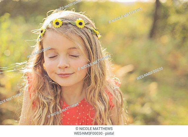 Portrait of relaxed little girl with eyes closed wearing flower wreath