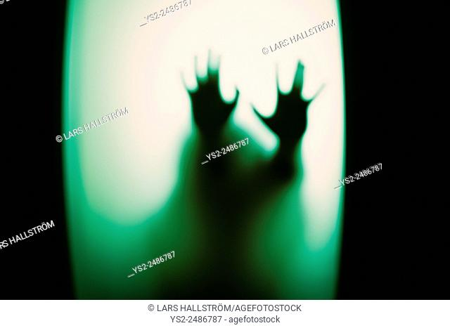 Silhouette of little child holding up hands. Conceptual image of childhood fears, abuse and safety of children