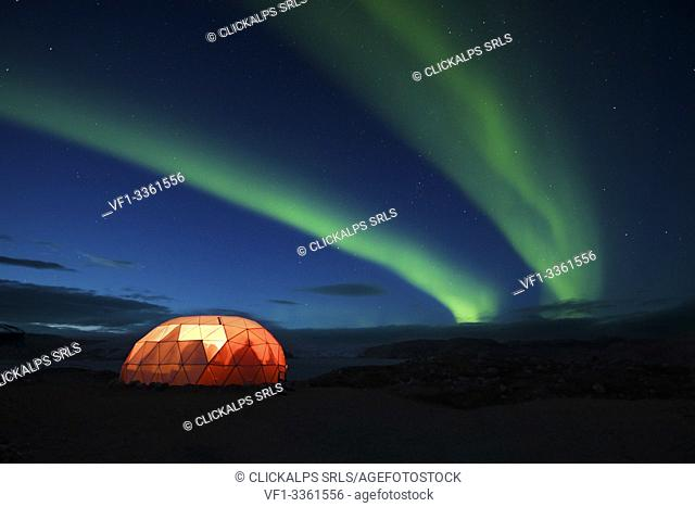Illuminated tent with northern Lights,Qaleraliq Glacier Camp, Greenland