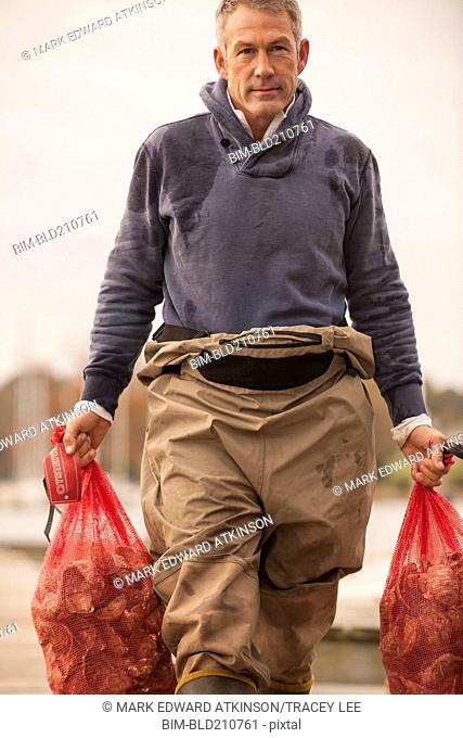 Caucasian fisherman carrying catch on dock